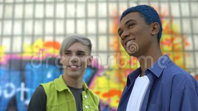 Jovens sorrindo em pé ao ar livre, construção de grafites, cultura urbana video estoque