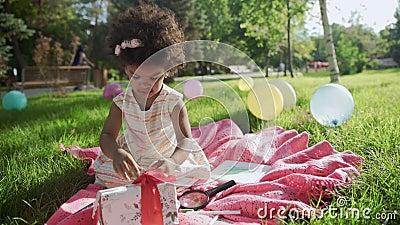 Joyeuse petite fille afro-américaine jouant avec la boîte à cadeau pour son anniversaire banque de vidéos