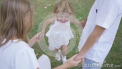 Joyeuse petite fille qui saute en tenant les parents la main dans le parc Un enfant passe du temps en famille Enfance clips vidéos