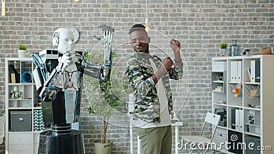 Joyeux Africain-Américain dansant avec un robot à l'aspect humain au bureau s'amusant banque de vidéos