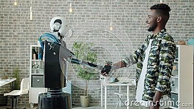Joyeux Africain-Américain serrant la main à un robot similaire sur son lieu de travail banque de vidéos