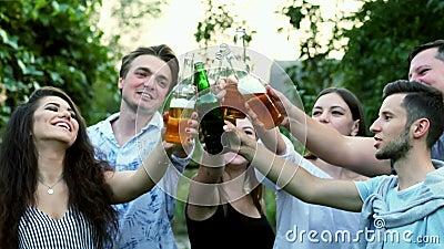 Joyeux jeunes amis qui s'amusent ensemble à boire de la bière et des verres clinquants banque de vidéos