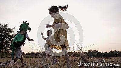 Joyeux passe-temps, un enfant masculin en costume de dragon joue à un jeu actif avec des amies qui courent autour du pré au couch banque de vidéos
