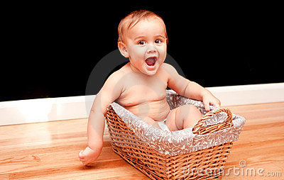 Joyful 9 month old baby in basket