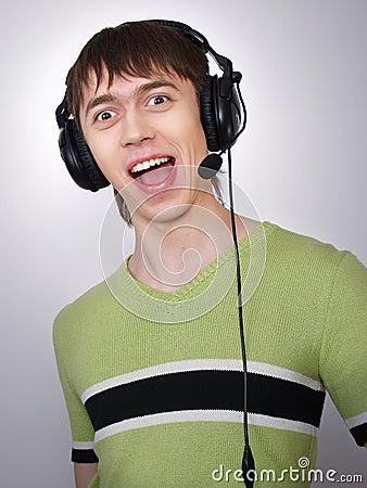 The joyful active boy in ear-phones sings