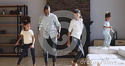 Joyful ative afro american Family dançando saltando na sala de estar