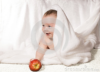 Joyful baby with red apple  under a white blanket