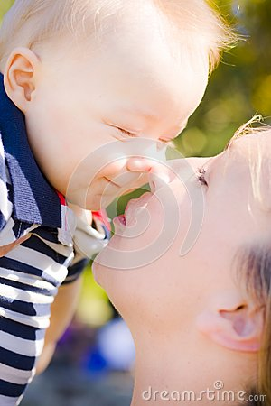 Joyful baby rubbing noses with Mom