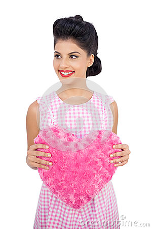 Joyful black hair model holding a pink heart shaped pillow