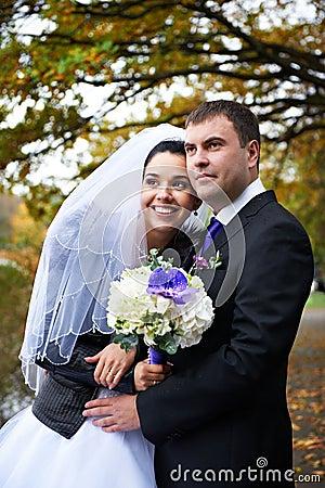 Joyful bride and groom in autumn park