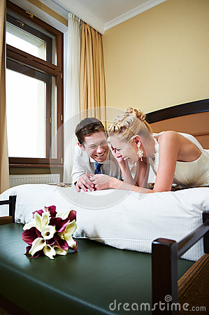 Joyful bride and groom in bedroom