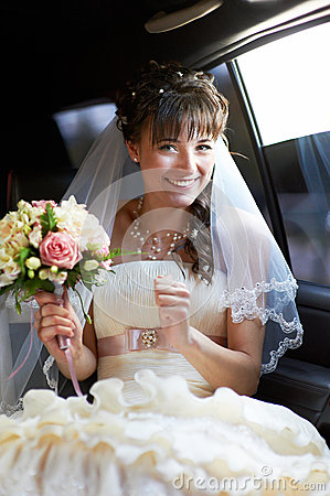 Joyful bride into limo