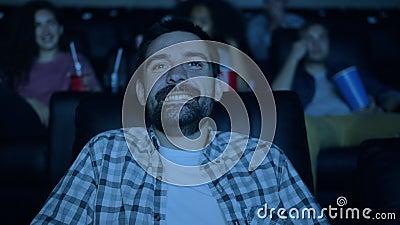 Joyful brunet assistindo um filme engraçado no cinema rindo se divertindo na sala escura filme
