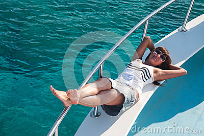 Joyful brunette woman laying on yacht deck