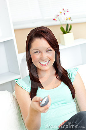 Joyful caucasian woman holding a remote smiling