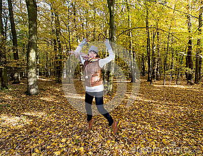 Joyful caucasian woman jumping in the autumn leaves