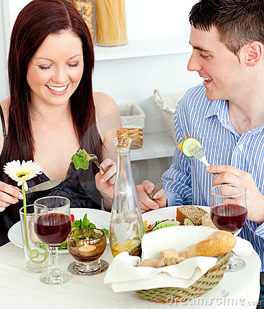 Joyful couple eating salad