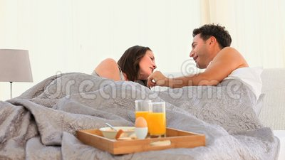 Joyful Couple having Breakfast in bed Stock Photo