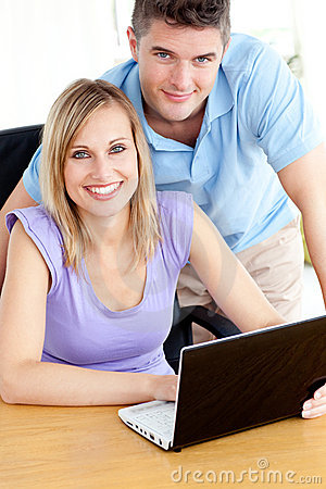 Joyful couple using a laptop in the kitchen