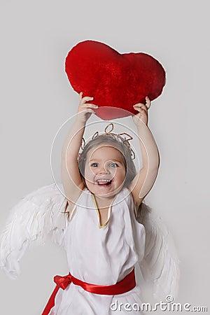 Joyful cupid girl holds plush heart over head