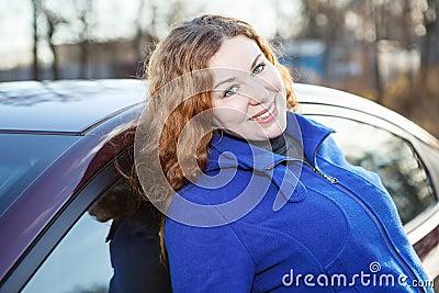 Joyful curly hair woman leaned against car