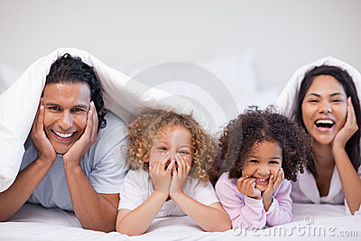 Joyful family hiding under the blanket