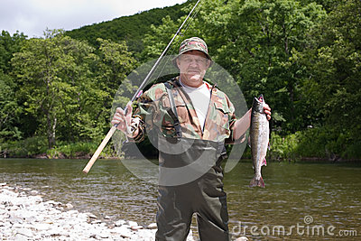 Joyful fisherman holding pink salmon.