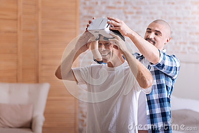 Joyful friends playing with the virtual reality glasses Stock Photo