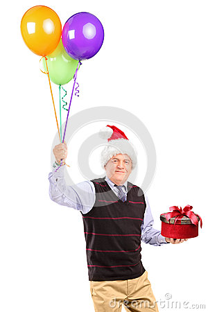 Joyful gentleman holding gift and balloons