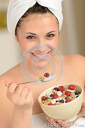 Joyful girl eating muesli for breakfast