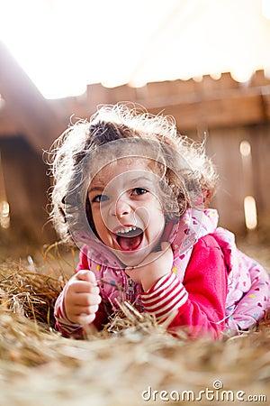 Joyful Girl in Hay Laughing