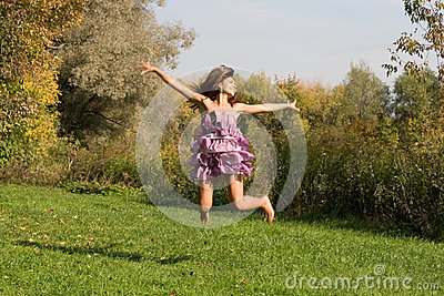 Joyful girl jumping on meadow