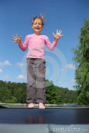 Joyful girl jumps on trampoline