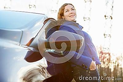 Joyful girl leaned against car