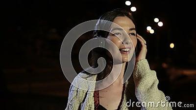 Joyful girl listening music with earphones at night stock footage