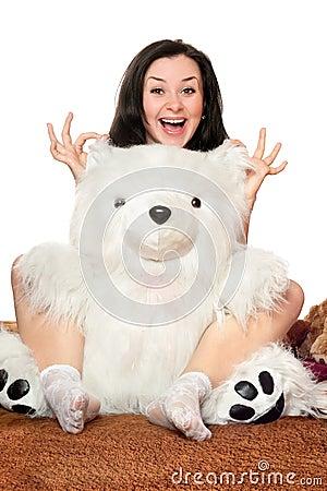 Joyful girl plays with a teddy bear