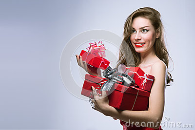 Joyful girl in red dress with gifts