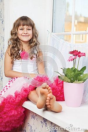 Joyful girl teenager sitting on windowsil in room