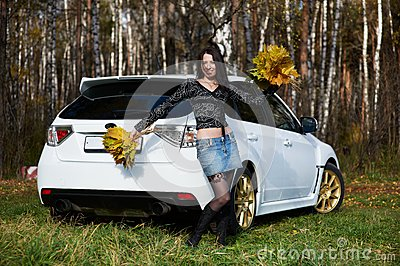 Joyful girl with yellow leaves and white car