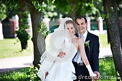 Joyful groom and bride in park
