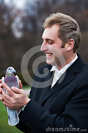 Joyful groom with pigeons on hands