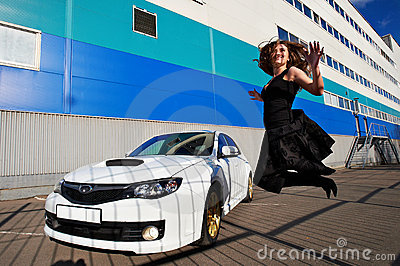 Joyful happy girl jumping near white car