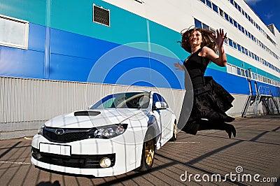 Joyful happy girl jumping near white car