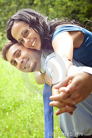 Joyful happy young couple playing outdoor