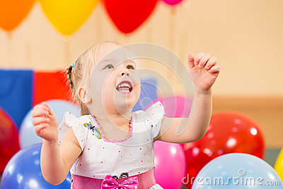 Joyful kid girl with balloons on birthday party