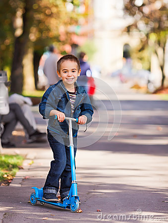 Joyful kid riding a scooter