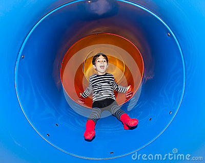 Joyful kid sliding in tube slide