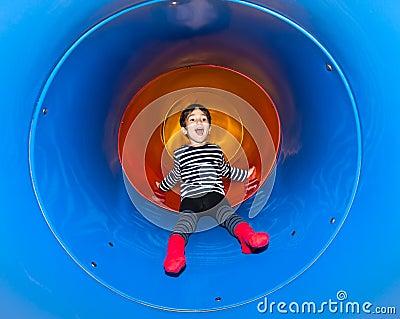 Joyful kid sliding in tube slide