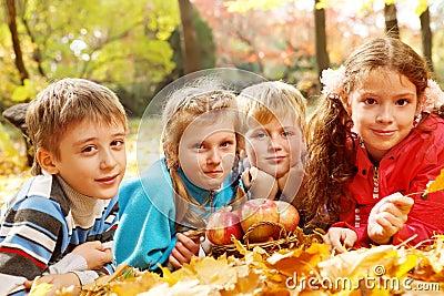 Joyful kids lying on autumnal leaves