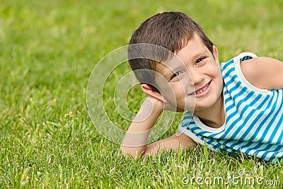 Joyful little boy on the grass